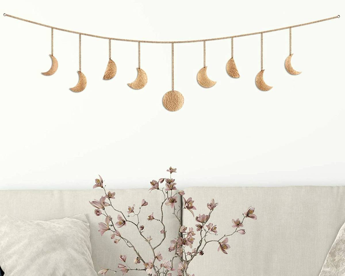Similarly to the wall art we've mentioned above, celestial wall hangings add something to the room. The texture a wall hanging adds can really be transformative. You'll see the beauty in the stitching and you can even have a go at making your own. These can be in fabric format, but you can also use a large wooden or metal moon wall hanging to bring some life to the space. To be even more creative, get some thick cardboard and cut a moon from that before prepping and spray painting it silver. This will be one of the cheaper ways to add moon decor to the home.